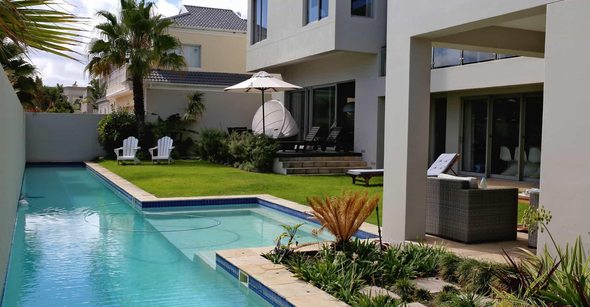 Gästehaus Aussenbereich mit Pool und Liegen - guesthouse pool with garden